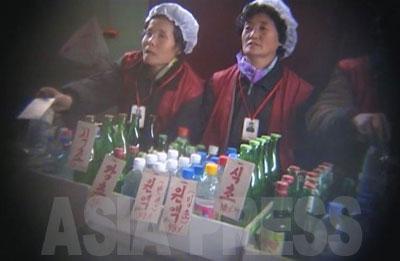 通路の上部には、それぞれの売り場の案内板がかけられている。ここは食酢売り場。北朝鮮の酢は穀物や果物を醸造したものではなく、ビンチョ酸と呼ばれる化学合成物の原液を水で薄めたもので、味が悪いとリ・サンボン氏は言う。様々な濃度で売られているが、濃いものだと口がただれることもあるとのことだ。ビンチョ酸は咸鏡南道の興南(フンナム)肥料工場などで生産されるという。原液も売られていることが映像からうかがえる。