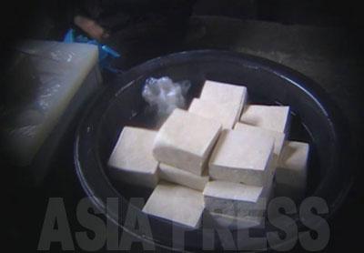 自家製の豆腐。北朝鮮を脱出して日本や韓国に住む人たちの多くが、北朝鮮が誇れる数少ないものの一つが豆腐であると語る。北朝鮮のものの方が味が濃くおいしいという。当時1丁200ウォン(約5円)で売られていた。