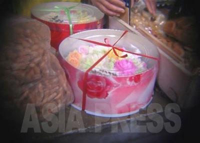 デコレーションケーキは当時の金額で22000ウォン(約550円)。高価ではあるが、子どもの誕生日を大事にする北朝鮮では案外売れるという。ケーキはすべて手作り。ピンク色のバラの包み紙にくるまれ、赤と緑のリボンで留められている。ケーキの上のクリームも白、紫、オレンジ、緑と色とりどりで豪華に見える。平壌の中でも幹部が多く住む地域にある市場だからこその品だ。