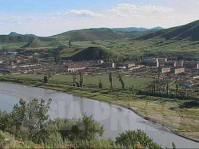 豆満江を挟んで中国から望む游仙の街。ボタ山に草が生えている。撮影時、ほとんど何の音も聞こえて来なかった。(2004年8月 石丸次郎撮影)