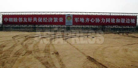 黄金坪の入口に立てられた大型看板には「中朝善隣友好で共に経済繁栄を促進」「軍民が心を合わせて協力し調和的な国境を建設」と書かれている。2012年 3月 南正学(ナム・ジョンハク)撮影