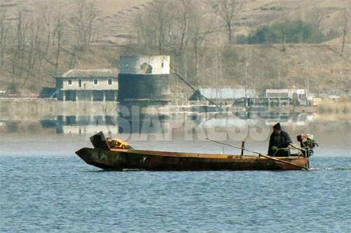 漁をしていると思われる船が一艘、川に浮かんでいた。