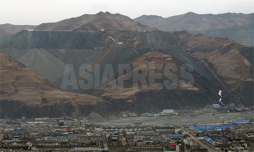 中国側から見た茂山鉱山。可採量は数十億トンと上るとされる、アジア最大級の鉄鉱山。多くの鉄鉱石(精鉱)を中国へと輸出していることで知られる。昨年5月の取材当時には見られなかった、輸送管のような建造物が新たに設置されていた。2012年3月 南正学(ナム・ジョンハク)撮影(アジアプレス)