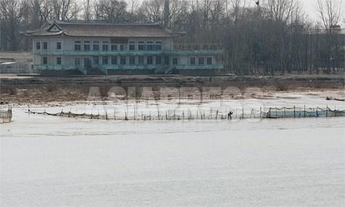 漁師たちが漁網を手入れしている。後ろに見える瓦葺きの建物は「鴨緑江閣」。新義州を訪れる北朝鮮の幹部が会議や宴会を開く所とされる。壁の塗装もはげ、周囲には雑草も生い茂っており、現在も使われているのか定かでない。 2012年 3月 南正学(ナム・ジョンハク)撮影