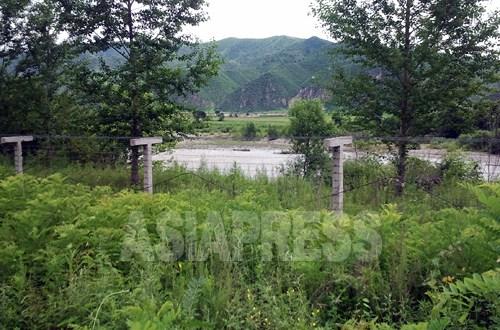朝中国境の川・豆満江沿いでは、鉄条網の増設が続いている。写真は吉林省の龍井市三合鎮に張られた鉄条網。対岸は北朝鮮の会寧市。2012年7月30日 パク・ヨンミン撮影(アジアプレス)