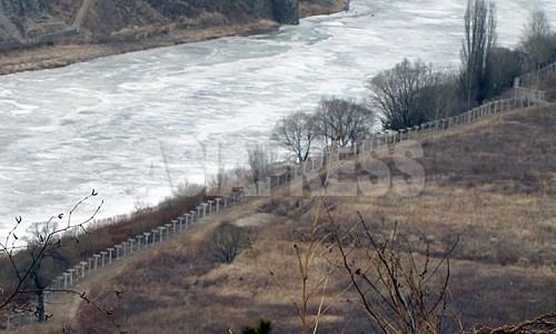 中国側の吉林省和龍市南坪鎮に新たに設置された鉄条網。凍った川が豆満江。対岸が咸鏡北道茂山(ムサン)郡だ。2012年3月南正学(ナム・ジョンハク)撮影