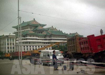 中心部の中区域、第一百貨店前の臨時の「人民武力部駐車場」に集結した工事用車両。中国製のダンプカーや日本の「加藤製作所」製のクレーン車などが並んでいる。