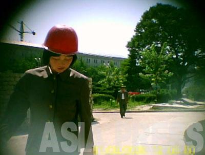 このヘルメット姿の女性も動員された青年同盟突撃隊員。