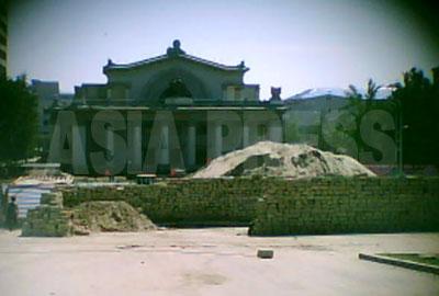 小さなコンクリートブロックが日干しされている。背後にセメントと混ぜる砂山。
