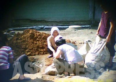 市内の歩道の補修工事もあちこちで見られる。古い敷石ブロックの取り替え作業。引き剥がした古いブロックなどの瓦礫を片付けている。作業しているのは、人民班で動員された周囲のアパートに住む住民たちだ。