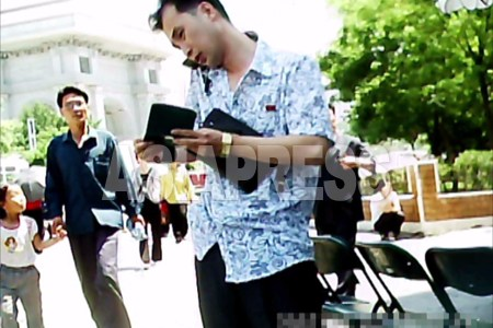 手帳をめくりながら携帯電話を使う男性。場所は平壌市の中心部、背後に凱旋門が見える。(2011年6月牡丹峰(モランボン)区域 ク・グァンホ撮影)