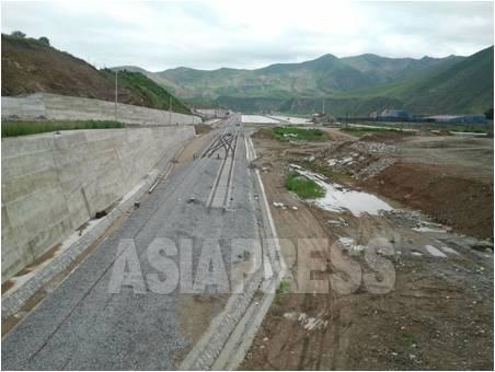 中国の吉林省・延辺朝鮮族自治州に建設されている「和坪鉄道」。奥の白い場所が南坪鎮の駅舎。背後の山並みは北朝鮮。今月5日、パク・ヨンミン撮影(アジアプレス)