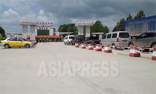 羅先(ラソン)市を目指す数十台の車が通関を待っている。ここから羅津(ラジン)港までは50キロほどだ。左側には北朝鮮からの訪問者と帰国者を待つタクシーも見える。7月6日、中国吉林省琿春市の圏河税関にて。撮影:パク・ヨンミン(アジアプレス)