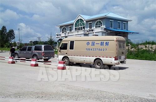 北朝鮮観光用と思われるマイクロバスも通関待ちしている。羅津市までは道が悪いため、現在、中国側が費用を負担し、高速道路が建設されており、完成は近いとされる。7月6日、中国吉林省琿春市の圏河税関にて。撮影:パク・ヨンミン(アジアプレス)