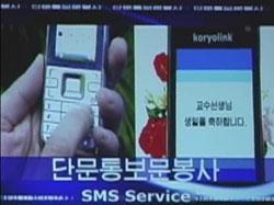 テレビで携帯電話の「短文通報文奉仕」(メッセージ)が紹介された。画面には「教授先生 誕生日おめでとうございます」とある。(朝鮮中央テレビより引用  2008年12月)