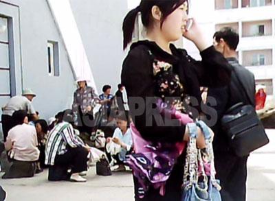 市場(ジャンマダン)の開場を待ちながら、携帯電話で通話する女性。富裕層の子弟たちのあいだでは、携帯電話は高い人気があるという。(2010年6月平壌市中区 ク・グァンホ撮影)