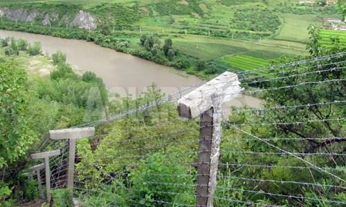 豆満江を挟んで、咸鏡北道会寧(フェリョン)市を臨む高台に新たに増設された鉄条網。傾斜が急であるにも関わらず隙間なく設置されている。2012年9月 ナム・ジョンハク撮影(アジアプレス)
