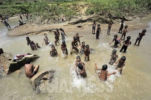 雨期まっただ中の貴重な晴れ間、歓声を上げて水浴びをする、ロヒンジャの非公式難民キャンプの子どもたち(2012年8月撮影:宇田有三)