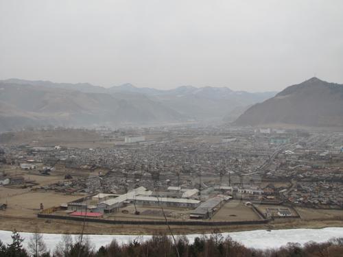 (参考写真)朝中国境に位置する咸鏡北道茂山(ムサン)郡。手前に見える豆満江を挟んで中国と向かい合う。ここでは中国キャリアの携帯電話が使用可能なため、北朝鮮内部情報の一大発信地となっている。2012年3月中国側から撮影(アジアプレス)