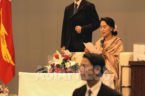事前にメモのかたちで集められた在日ミャンマー人の質問を読み上げるスーチー氏(2013年4月13日 東京・渋谷)
