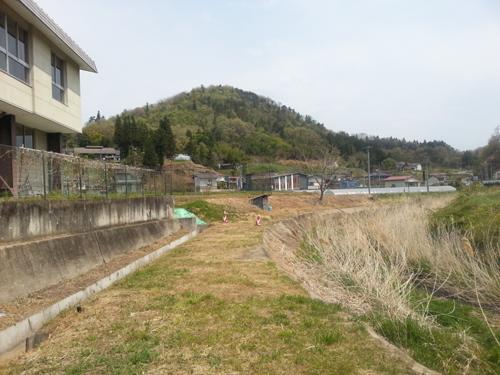 小国小学校の校庭の裏側には堤と小川。高い放射線量を記録した(2013年5月 伊達市小国地区)