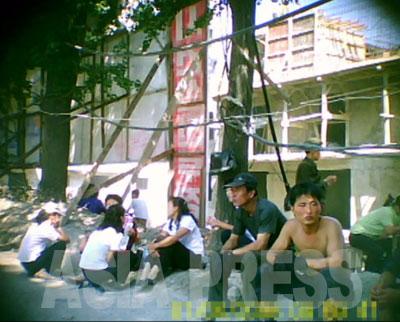 工事に動員された人々。左側は女子大学生だ。右の二人の男性は海外で建設事業を請け負い外貨稼ぎを行う「対外建設」所属の労働者だと思われる。休憩中なのか単に油を売っているだけなのかは不明。2011年8月平壌市大同江区域 撮影:具光鎬(ク・グァンホ)記者(アジアプレス)