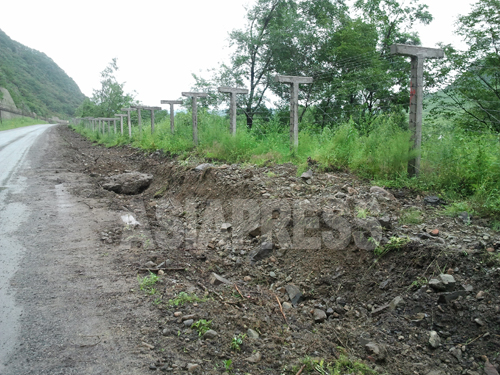 豆満江沿いを走る道路に設置された鉄条網。豆満江下流の琿春市にて7月31日撮影。写真パク・ヨンミン/アジアプレス