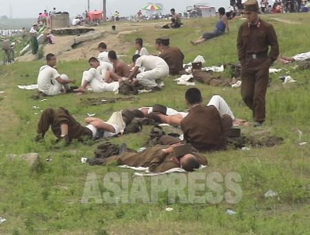 公園で休日を楽しむ住民の横で休憩中の兵士たち。「庶民より兵士の方が元気がない。腹を減らしているから」と撮影者のリ・ジュンは言う。(撮影:2006年8月清津市)