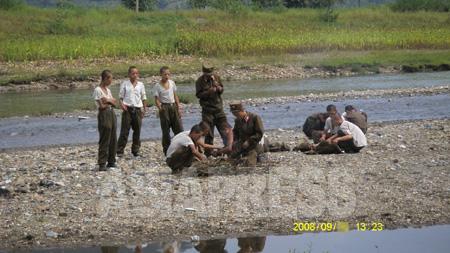 軍の末端の兵士に食糧は行き届いておらず、栄養失調の兵士も少なくない。農家や庶民から食糧を奪う事件も起きているという。写真は畑からトウモロコシを盗んで河原で焼いて食べる人民軍の兵士。痩せている姿が目に付く。2008年9月 撮影 張正吉(チャン・ジョンギル)