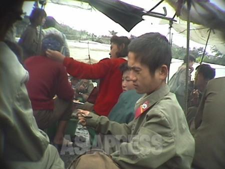 闇市場で空腹を満たす兵士。(1998年10月 元山市 撮影アン・チョル)