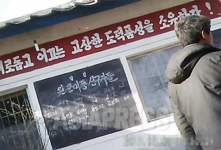 平壌市郊外の公設市場入り口に掲げられた黒板には「援軍美風の先駆者たち」と大書きされ、商人の名前と扱う品目、そして「献納」した軍糧米の量が記されている。(2011年2月 キム・ドンチョル撮影)