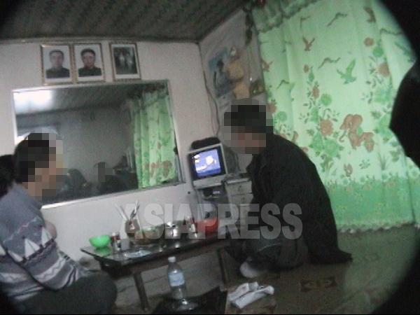 北朝鮮のすべての家庭と職場、公共の場所(ジャンマダンを除く)には、金日成と金正日親子の肖像画が掲げられている。写真は清津(チョンジン)市内のとある家族の食事風景。金親子の肖像画に加え、金正淑(金正日の母)が描かれた肖像画が見える。2007年4月 李準(リ・ジュン)撮影(アジアプレス)