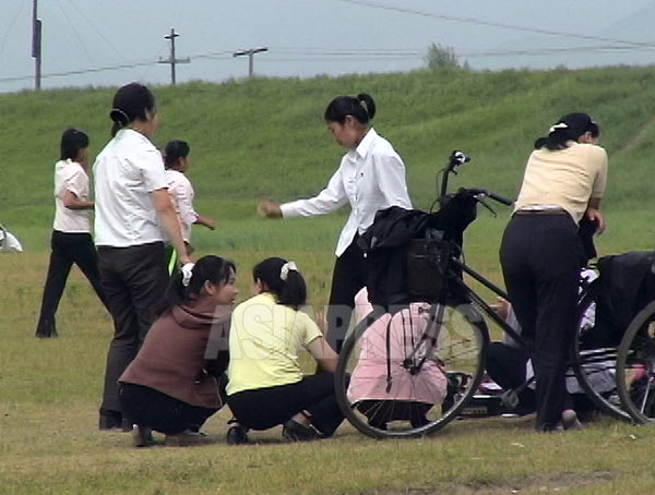 休日の公園でラジカセで音楽を流しながらディスコ風ダンスに興じる若者たち。外部世界の影響を受けているのは明らかだ。ただし公の場でかけられるのは北朝鮮の曲だけ。女性はポニーテールをリボンで括るのが流行っていたようだ。(2006年8月清津市 リ・ジュン撮影)