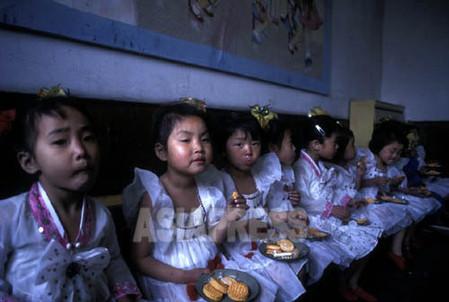 お菓子を食べている羅津(ラジン)市模範託児所の子供たち 1998年3月 石丸次郎撮影
