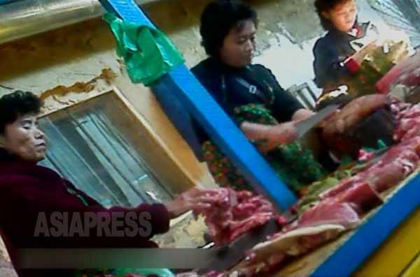 豚肉を切り分ける商売人の女性たち。2012年11月北朝鮮北部の国境都市の市場で。撮影アジアプレス(以下2枚も同様)。
