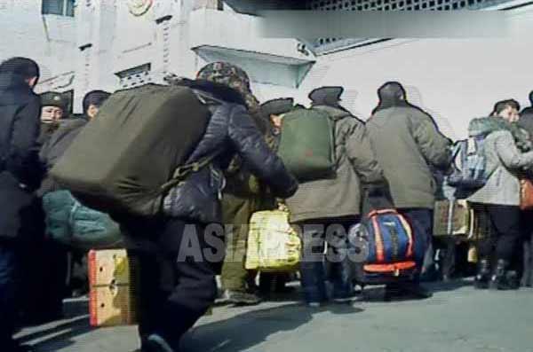 大荷物を持った人々でごった返す鉄道駅。手前の年配の女性は前傾姿勢をとって荷物の重さとバランスをとっている。2012年11月平安北道新義州(シニジュ)駅、撮影 アジアプレス