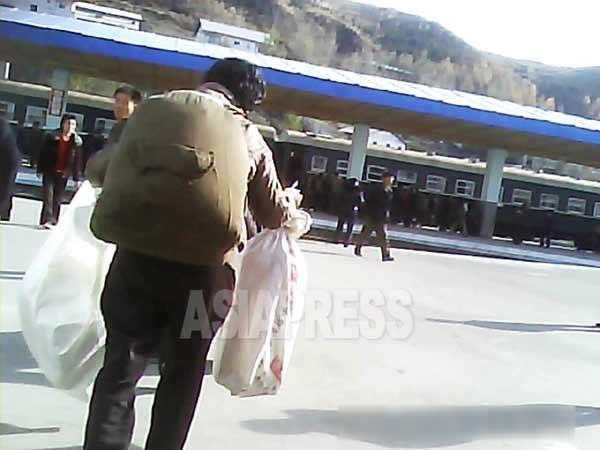 列車に遅れまいと急ぐ女性。ぎっしりと物が詰め込まれた大きなリュックを背負い、両手には布袋を持って走る。2013年10月北部のとある国境都市、撮影 アジアプレス