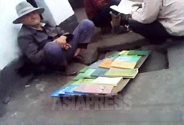 年配の男性が道端に座り込み、本を売っている。2013年11月咸鏡北道清津市のある市場、撮影 アジアプレス