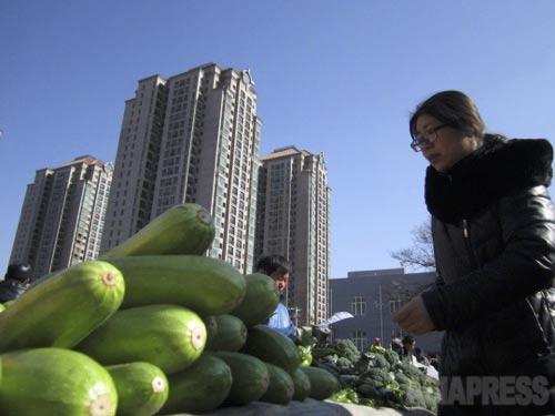 小さな市場の周りには高いビル。2014年2月19日、北京・朝外北街にて。撮影 宮崎紀秀