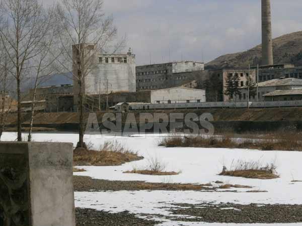 国境の川・鴨緑江を挟んで恵山市内の工場が見える。建物は古び煙突から出る煙も見えない。(写真:アジアプレス)