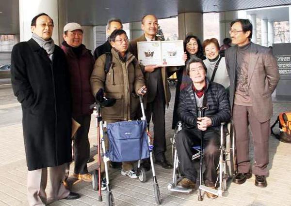 ソウル高裁で無罪判決後、日本からの支援者に囲まれる李さん(右から5人目)=畑章夫さん 1月撮影