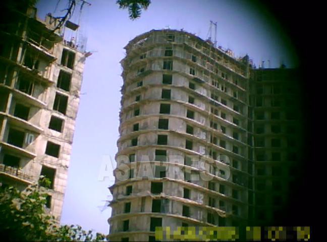 平壌中心部で建設されていた20階を超える高層アパート。各階を手積みする北朝鮮独特の「ブロック工法」で建てられている。各階の窓枠の位置も大きさもまちまちで歪んでいる。2011年8月平壌市大同江区域 撮影:具光鎬(ク・グァンホ)記者(アジアプレス)