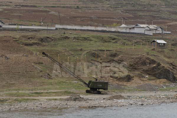 鴨緑江に沿って、鉄条網設置のための柱が建てられている。右上の小屋は国境警備隊の詰所。場所は恵山市のカング洞