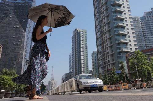 日焼けを気にする女性には、日傘は必需品?。 撮影日 2014年5月29日 撮影場所 金桐西路 撮影 宮崎紀秀