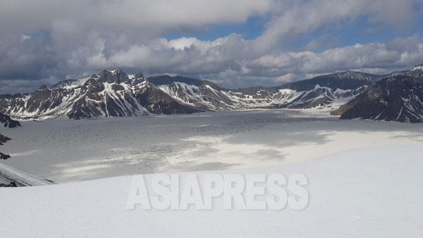 雪に覆われた白頭山頂上にあるカルデラ湖の天池。朝鮮民族発祥の伝説がある。北朝鮮側の山々が見える。5月下旬 撮影 朴永民/アジアプレス