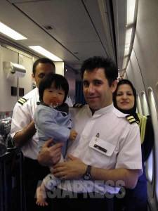 今はなき東京―テヘラン直行便の機内にて、客室乗務員に抱きかかえられる息子。この後、おもちゃやジュースなどを頂く。(撮影筆者/2008年)