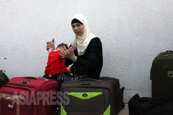 一時停戦の朝、人々がガザから出ようとしていた。ラファの境界で出国の許可を待つヌールさんと娘(2014年8月12日 撮影 古居みずえ)