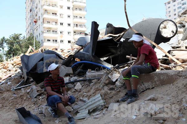 イスラエル軍に家を爆破されたアベッド君と従兄弟のオマル君。「何か残っていないかと来てみたけど、服が少し見つかっただけ」とアベット君は肩を落とした。(8月25日ガザ市内で撮影・古居みずえ