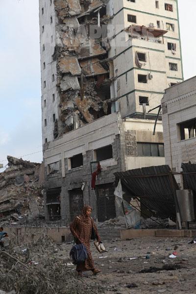 靴と荷物だけ持って避難する女性。後ろが壊された14階建の集合住宅(8月26日ガザ市内で撮影・古居みずえ