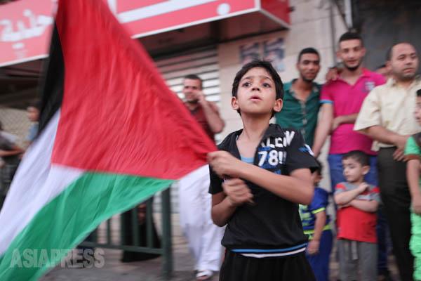8月26日、イスラエルとハマスは長期的停戦を結び、人びとに笑顔が戻った。写真はパレスチナの旗を振る少年。(8月26日ガザ市内で 撮影・古居みずえ)